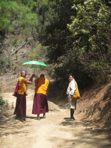 two monks with sunshade on their way up