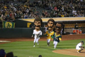 some kind of entertainment involving oversized bobble heads running 1/2 way around the field.